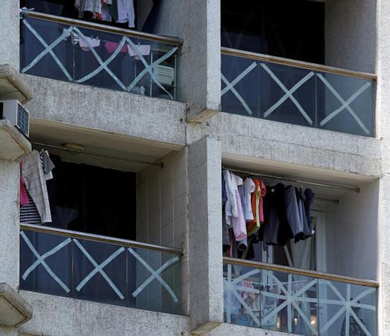 """△15日,香港,随着台风""""山竹""""逼近,当地民众纷纷在建筑和车辆的玻璃上贴满胶带,防止玻璃碎裂伤人。(图自视觉中国)"""