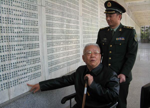 """张斌指着刻在淮海战争留念馆勇士墙上自己的姓名,笑称自己是""""活勇士""""。"""