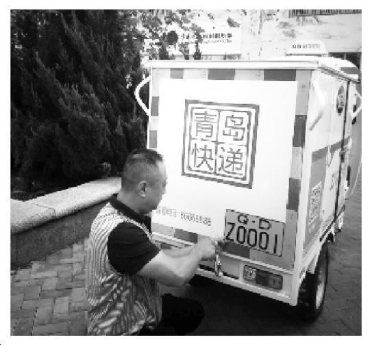 图为工作职员给快递三轮车安置标识。孙安清 曲海青 栾心龙 摄