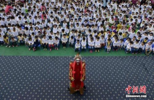 """资料图:京剧进幼儿园,""""财神""""为孩子们表演下腰。 杨华峰 摄"""