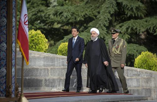 资料图片:2019年6月12日,在伊朗首都德黑兰,伊朗总统鲁哈尼(中)与到访的日本首相安倍晋三(左)参加欢迎仪式。新华社发