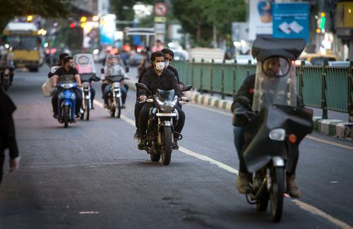 4月29日,在伊朗德黑兰,一名男子骑车时戴着口罩。新华社发(艾哈迈德·哈拉比萨斯摄)