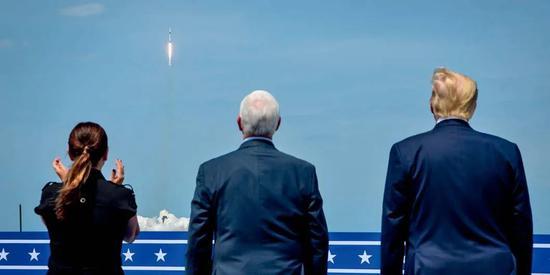 """5月30日,在美国佛罗里达州肯尼迪航天中心,美国总统特朗普(右)和美国副总统彭斯(中)等观看载人版""""龙""""飞船搭乘""""猎鹰9""""火箭升空。"""