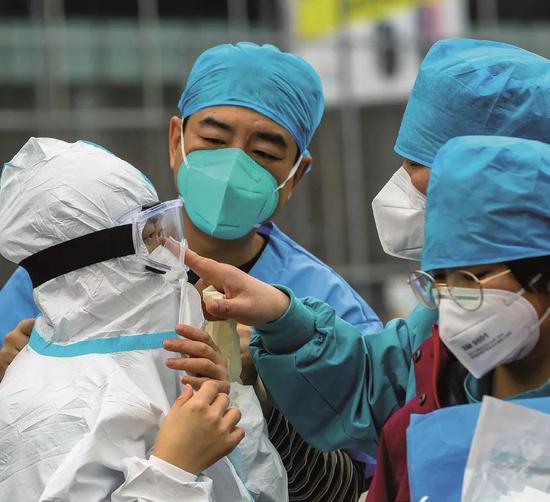2020年2月12日,武汉江岸塔子湖方舱医院医护职员做好防护事情筹办进舱。图/中新
