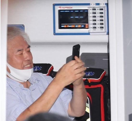 牧师全光勋确诊后,在救护车上开心玩手机(韩联社)