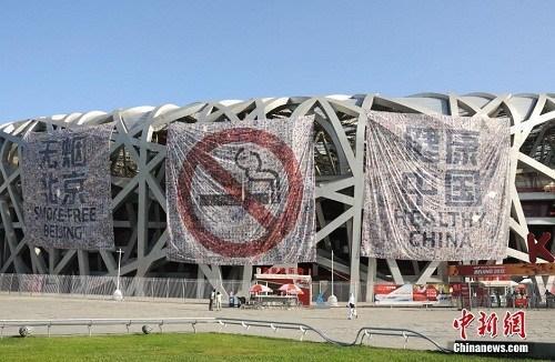 """资料图:2019-06-26,北京奥林匹克公园,""""鸟巢""""悬挂起巨幅禁烟标志及禁烟标语,迎接5月31日""""世界无烟日"""" 的到来。中新社发 玉龙 摄 图片来源:CNSPHOTO"""
