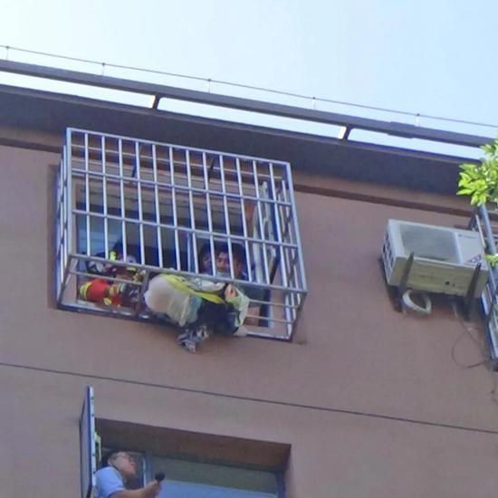 惊险!七岁女童悬挂窗外 民警和消防员拆护栏救孩子