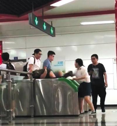 翻 两男子用双手撑住地铁检票闸机两侧,纵身翻过闸机口。视频截图
