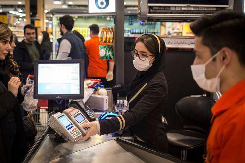 3月5日,在伊朗德黑兰,商场收银员佩戴口罩工作。新华社发(艾哈迈德·哈拉比萨斯摄)