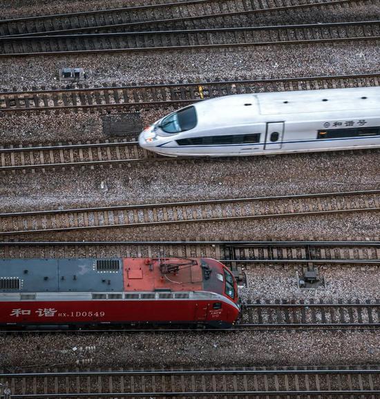 """中国将""""设想时速250千米及以上,且早期运营时速没有小于200千米的客运专线铁路""""界说为下铁;下图为正在上海站相逢的""""协调""""电力机车取""""协调号""""动车组,拍照师@吕威/星球研讨所"""
