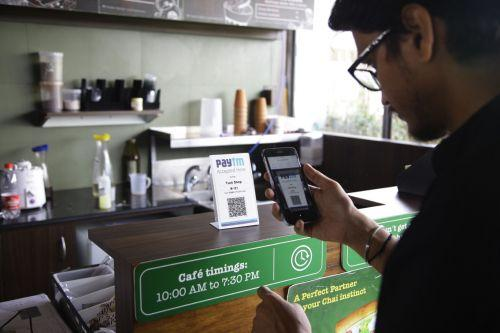 图说:在印度一家咖啡店,一名顾客正在使用paytm完成支付