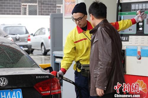 资料图: 哈尔滨市一加油站内,车主排队加油。中新社记者 于琨 摄
