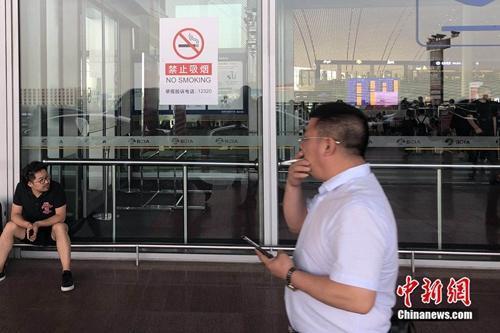 5月25日,一男子在北京首都机场的禁烟标识下吸烟通过。 冷昊阳 摄
