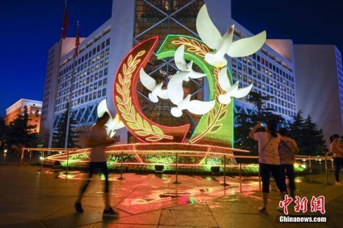 """8月31日晚,多处""""中非合作论坛北京峰会""""主题花坛点亮绚丽夜景灯光。图为西单路口西北角的""""合作共赢""""。中新社记者贾天勇 摄"""
