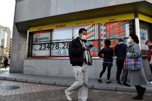 ▲2月21日,在日本东京,路人走过街边的电子股指信息显示屏。新华社/法新