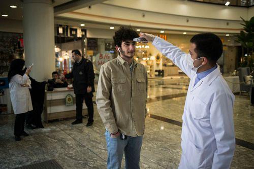 3月5日,在伊朗德黑兰,一名安保人员为进入商场的顾客测量体温。新华社发(艾哈迈德·哈拉比萨斯摄)