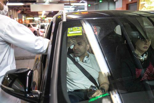 3月5日,在伊朗德黑兰,一名安保人员为出入商场停车场的顾客测量体温。新华社发(艾哈迈德·哈拉比萨斯摄)