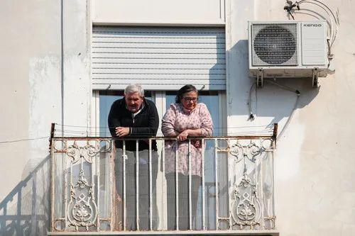4月10日,在意大利那不勒斯,两名老人站在自家阳台向外张望。新华社/路透