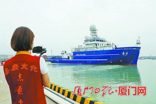 """昨日上午,""""嘉庚""""号科考船从厦门远海通达码头起航,一名嘉庚志愿者在岸边用手机拍摄离港情景。(记者 王协云 摄)"""