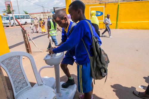 3月14日,在卢旺达首都基加利,儿童进入公交车站时洗手。新华社发