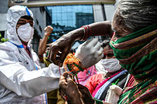 """8月3日,一名女士在印度孟买将彩绳系在医护人员的手腕上。当天是印度的传统节日""""保护绳节""""。新华社发"""