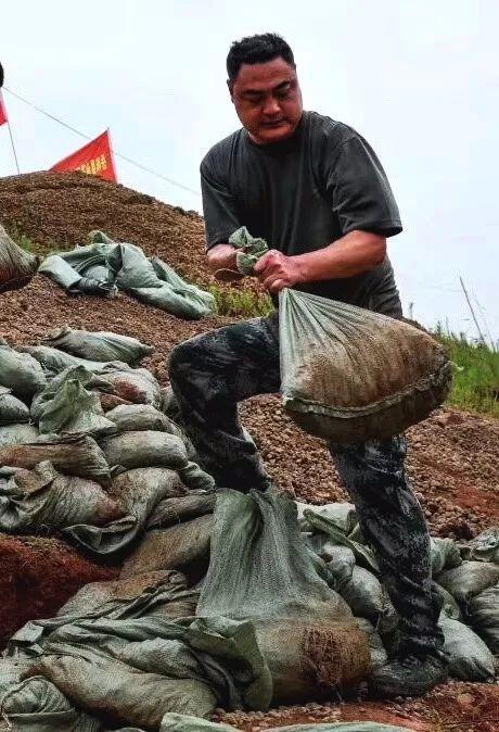 受持续强降雨影响,湖南岳阳县出现险情,退役军人火速抢险,安全护堤。图/文龙春涛周金良