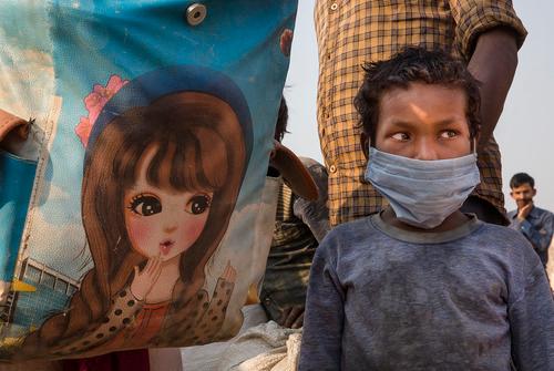 5月18日,在印度新德里郊区的加济阿巴德,一名儿童和家人一起排队等待登上返乡大巴。新华社发
