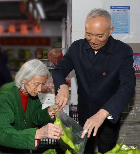 帮85岁高龄的吴慧英老人挑菜,询问菜价贵不贵