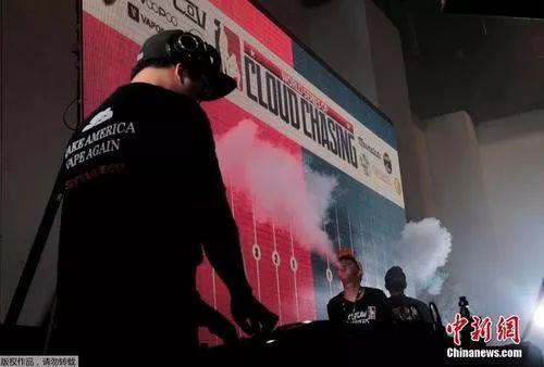 """资料图:电子烟交易大会,参与者们用电子烟进行""""吞云吐雾"""""""