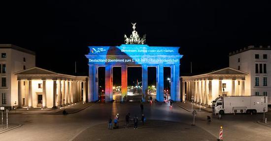 """△当地时间6月30日晚,柏林勃兰登堡门点亮""""共同携手复兴欧洲""""的标语,这是德国为其轮值主席国任期确定的口号。图:德国联邦政府/Plambeck"""