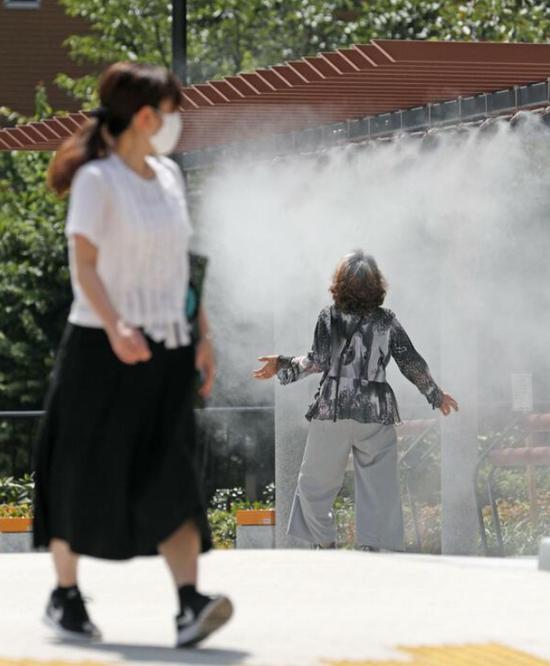 东京银座,人们用喷雾避暑(共同社)