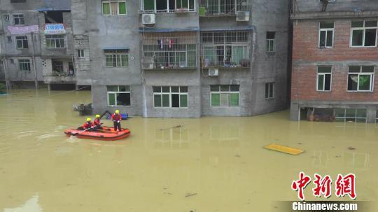 图为消防官兵划着橡皮艇达到被淹的楼宇邻近。 消防部分供图 摄