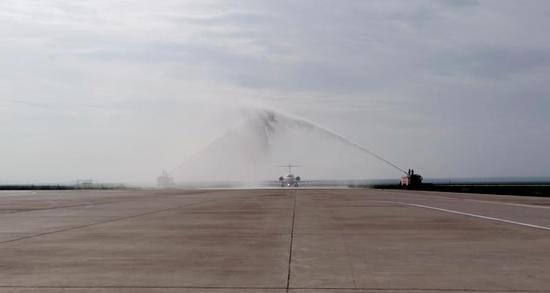 """飞机落地锡林浩特,当地机场用民航界最高礼遇""""过水门""""庆祝国航ARJ21飞机首航成功。陈灏摄"""
