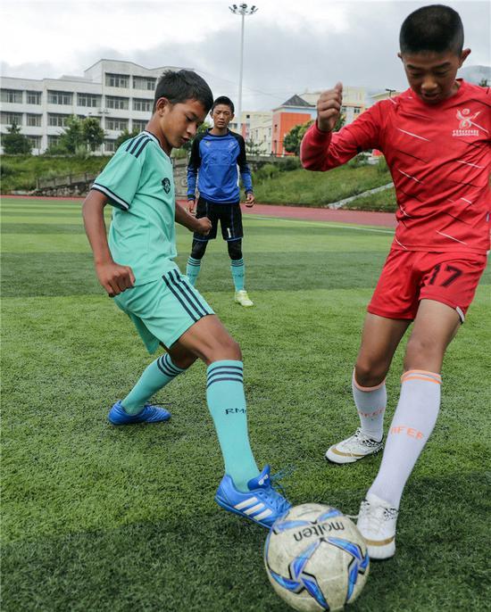 在四川省昭觉县拉莫足球场,阿作伍勒(左)在练习中拼抢(8月13日摄)。新华社记者沈伯韩摄