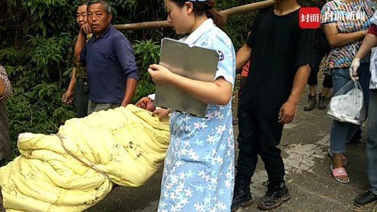 村民将受伤的彭章兴抬到山下的救护车。