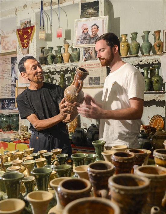 在喀什高台民居里,当地土陶艺人吐尔逊·祖农(左)在向来自澳大利亚的游客引见本人手工制造的土陶(7月11日摄)。新华社记者赵戈摄