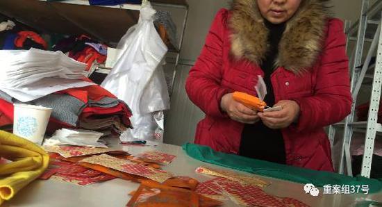 """▲3月2日,清河县东高庄村,一家专门给淘宝店铺供货的商铺。一名妇女正给一件针织衫贴上标注有""""羊绒""""含量""""85%""""、""""一等品""""、""""羊绒精品""""字样的标签。"""