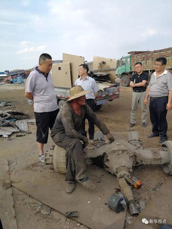 6月19日,督察职员在一家汽车拆解企业向任务职员懂得情形。新华社记者高敬摄