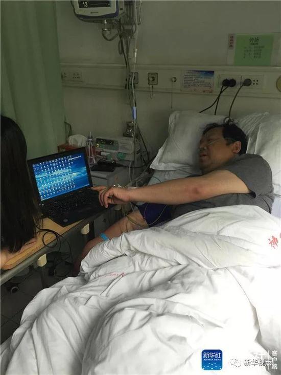 ↑钟扬教授在病房与同事交接工作(2015年资料照片)。新华社发(复旦大学供图)