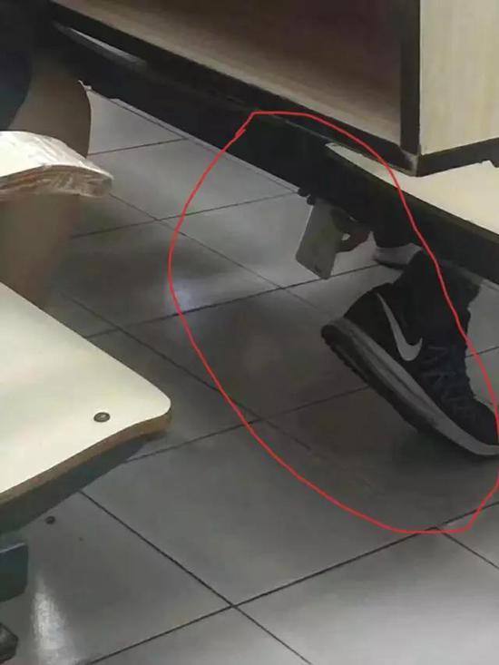 ▲男生以系鞋带的姿势,将手机后置摄像头伸到座位下方,试图偷拍。这一幕被教室内的其他同学当场记录。