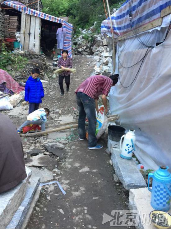 小廖(右一)在帮助村民搬东西。北京时间记者杨安平摄