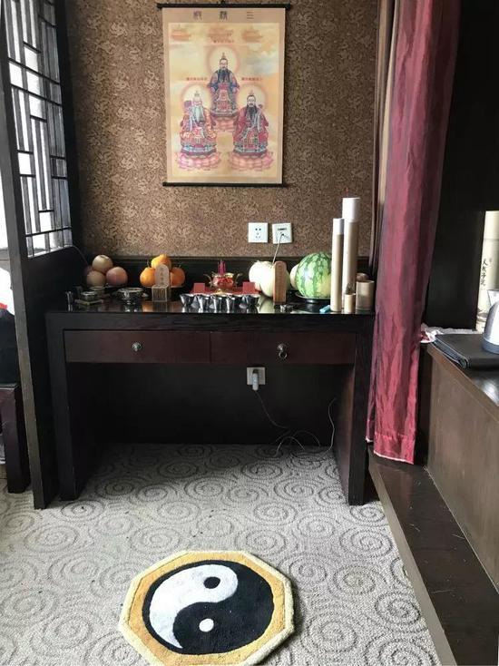 """宾馆房间的一处茶几上,供奉""""三精殿""""的祖师爷画像、""""混元雷祖""""牌位,香火、贡品、法水俱全,地上铺着八卦垫。"""
