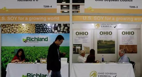▲此次中美贸易战波及美国大豆,图为在上海举行的国际大豆展览上,参观者走过美国大豆公司的展台。(美联社)