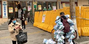 2月24日,在武汉市江岸区黄石路汉口大药房,为病人送药的小区事情者(右1)把为住民购置近100份的药挂全身上预备脱离。(图片泉源:新华社)