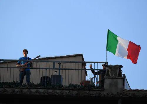 4月3日,在意大利首都罗马,一名男子在天台弹吉他。新华社发(阿尔贝托·林格利亚摄)