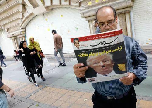 """▲一名伊朗男子手持刊载特朗普关于伊核协议讲话的报纸,标题为""""疯狂的特朗普""""。(法新社)"""