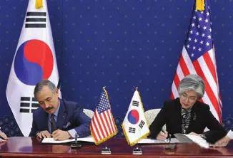 3月8日,首尔,韩国外交部长官康京和(右)与美国驻韩国大使哈里·哈里斯交换文件
