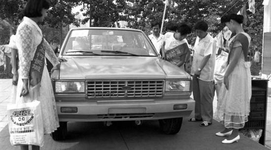 1990年第一届北京车展,长城汽车工业公司二分厂生产的轿车,人们新奇地围在车旁
