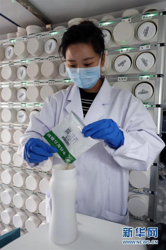 """2月26日,在武汉江夏方舱医院的""""活动应急智能中药房""""里,事情职员吴志婷往药瓶里添加单味中药浓缩颗粒。 新华社记者 沈伯韩 摄"""