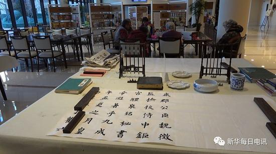 除夕前夕北京恭和家园展示老人墨宝,远处老人们共同制作春节礼物。邰思聪 摄